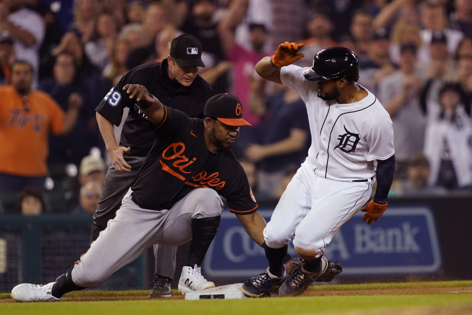 Detroit Tigers third baseman Jeimer Candelario beats the tag of Baltimore Orioles third baseman Maikel Franco (3) to advance on a wild pitch during the eighth inning of a baseball game, Friday, July 30, 2021, in Detroit. (AP Photo/Carlos Osorio)