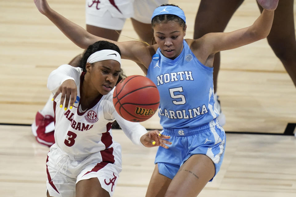 Alabama guard Jordan Lewis (3) passes in front of North Carolina guard Stephanie Watts (5) during the first half of a college basketball game in the first round of the women's NCAA tournament at the Alamodome in San Antonio, Monday, March 22, 2021. (AP Photo/Eric Gay)