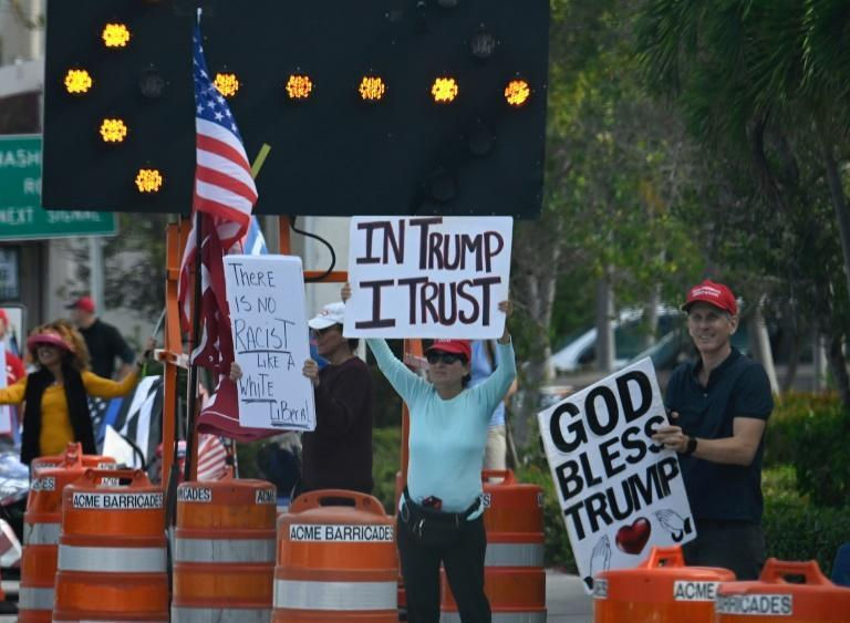 Supporters of US President Donald Trump hold up signs as the motorcade drives past after leaving the Trump International Golf Club in West Palm Beach, Florida