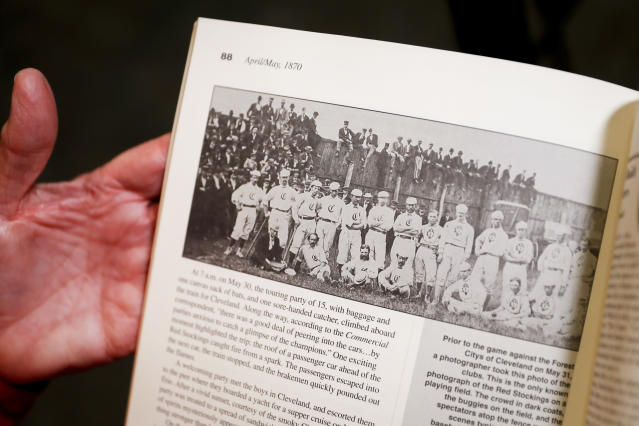 "Greg Rhodes, the Cincinnati Reds baseball team historian, holds a copy of The First Boys of Summer to a page showing a photograph of the Cincinnati Red Stockings in 1870 during an interview at the Cincinnati Reds Hall of Fame, Tuesday, Jan. 8, 2019, in Cincinnati. The Reds will play games in 15 sets of throwback uniforms, including navy blue and a ""Palm Beach"" style, during a season-long celebration of the 1869 Red Stockings who pioneered professional baseball. (AP Photo/John Minchillo)"