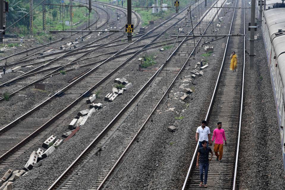 Passengers walk on a railway track after trains got stranded due to a major power cut in several areas after grid failure in Mumbai on October 12, 2020. (Photo by INDRANIL MUKHERJEE / AFP) (Photo by INDRANIL MUKHERJEE/AFP via Getty Images)