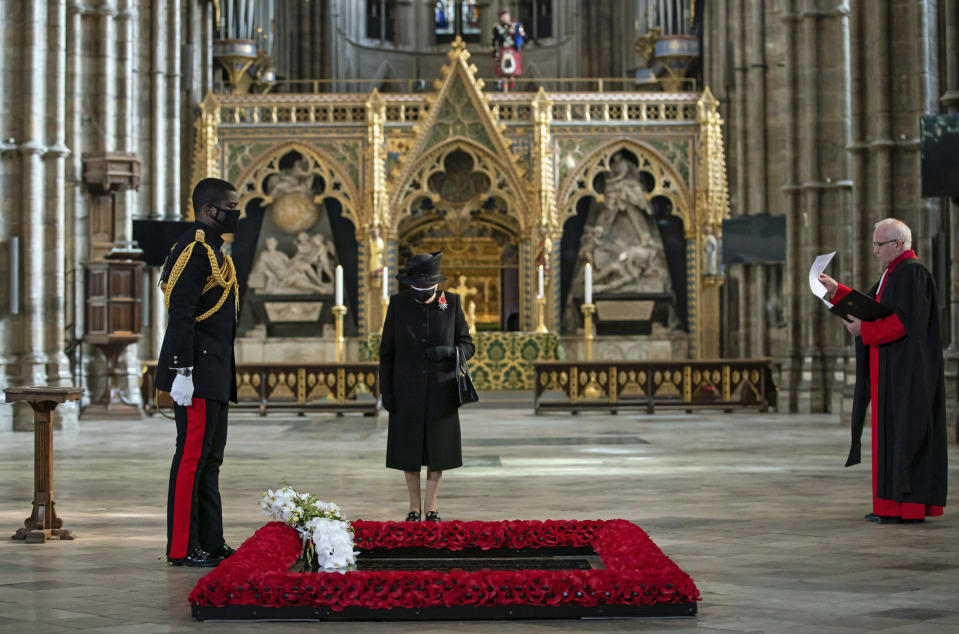 The Dean of Westminster Abbey David Hoyle, right, watches as The Queen's Equerry, Lieutenant Colonel Nana Kofi Twumasi-Ankrah, places a bouquet of flowers at the grave of the Unknown Warrior in front of Britain's Queen Elizabeth II, during a ceremony to mark the centenary of the burial of the Unknown Warrior, in Westminster Abbey, London, Wednesday, Nov. 4, 2020. Queen Elizabeth II donned a face mask in public for the first time during the coronavirus pandemic when attending a brief ceremony at Westminster Abbey last week to mark the centenary of the burial of the Unknown Warrior. While the 94-year-old has been seen in public on several occasions over the past few months, she has not worn a face covering. (Aaron Chown/Pool Photo via AP)