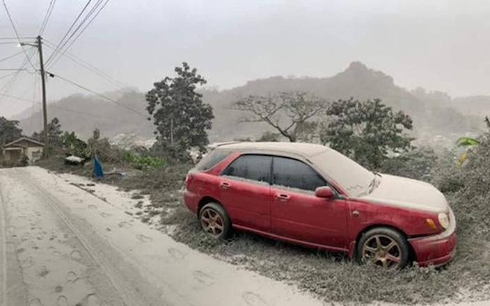 A car, road and scenery covered in ash - UWI Seismic Research Centre/AFP