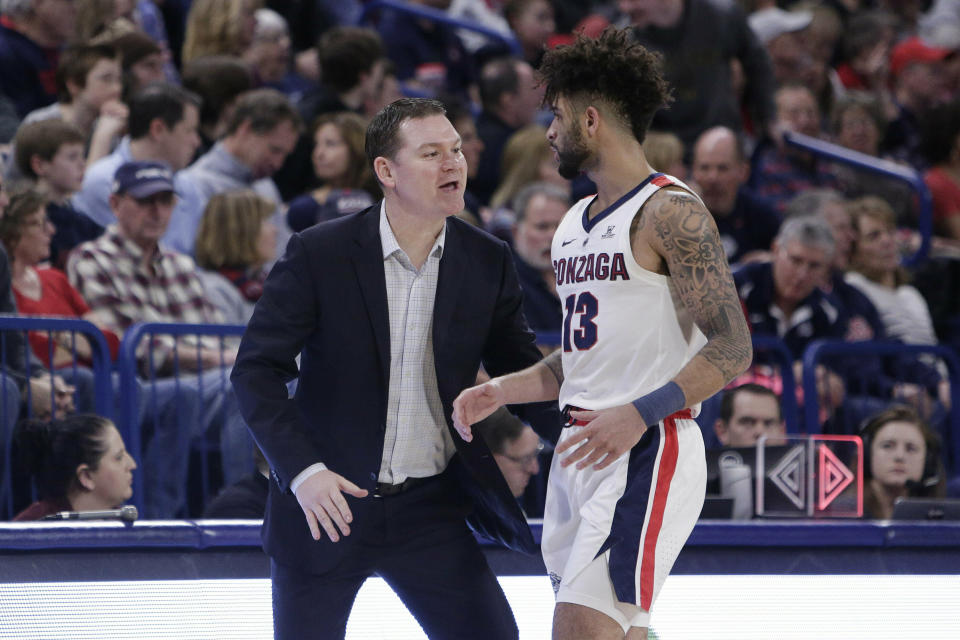 Gonzaga assistant coach Tommy Lloyd, left, speaks with guard Josh Perkins (13) during the first half of an NCAA college basketball game against San Diego in Spokane, Wash., Saturday, Feb. 2, 2019. (AP Photo/Young Kwak)