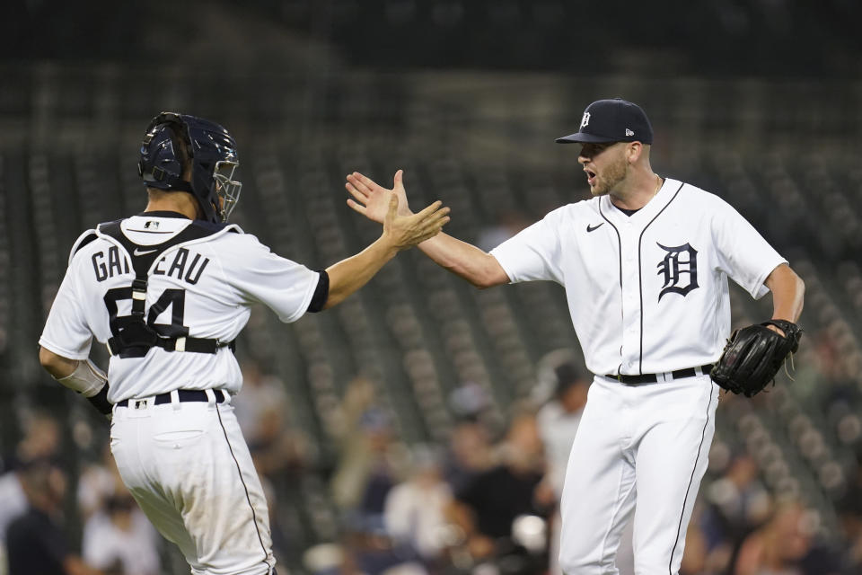 Detroit Tigers catcher Dustin Garneau (64) and pitcher Alex Lange celebrate after the final out in the ninth inning of a baseball game against the Chicago White Sox in Detroit, Monday, Sept. 20, 2021. Detroit won 4-3. (AP Photo/Paul Sancya)