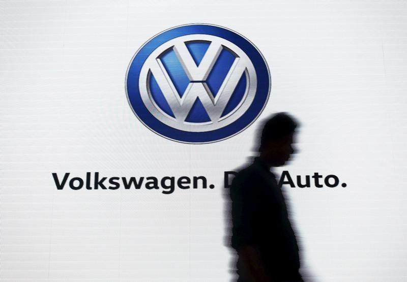 A man walks past a screen displaying a logo of Volkswagen at an event in New Delhi