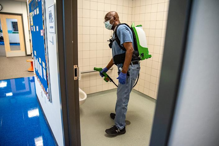 A custodian cleans a classroom at Akin Elementary in Leander, Texas, on Thursday. The school has been preparing for possible return of students by cleaning and disinfecting classrooms to help prevent the spread of coronavirus.