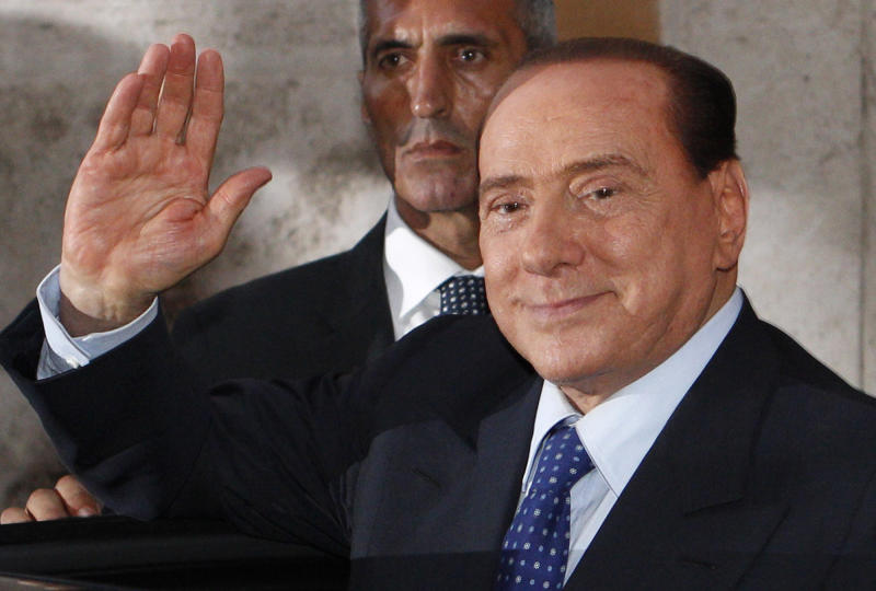 "Italian former Premier Silvio Berlusconi waves to reporters as he leaves after attending a meeting with the People of Freedom party's lawmakers at the Lower Chamber in Rome, Friday, Aug. 2, 2013. Italy's former premier, Silvio Berlusconi, for the first time in decades of criminal prosecutions related to his media empire was definitively convicted of tax fraud and sentenced to prison by the nation's highest court, Judge Antonio Esposito, in reading the court's decision Thursday, declared Berlusconi's conviction and four-year prison term ""irrevocable."" He also ordered another court to review the length of a ban on public office ó the most incendiary element of the conviction because it threatens to interrupt, if not end, Berlusconi's political career. (AP Photo/Riccardo De Luca)"