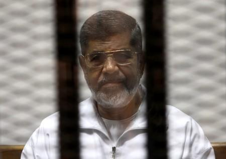 FILE PHOTO: Ousted Egyptian President Mursi is seen behind bars during his trial at a court in Cairo