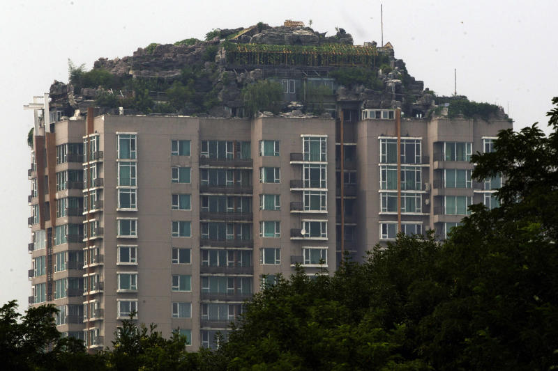 A rooftop villa complete with rocks and flora seen built on top of a high rise residential building stands in Beijing, China, Tuesday, Aug. 13, 2013. Beijing authorities are planning to demolish the bizarre rooftop villa embedded in rocks, trees and bushes that allegedly was built illegally atop a 26-story apartment block in the capital.(AP Photo/Ng Han Guan)