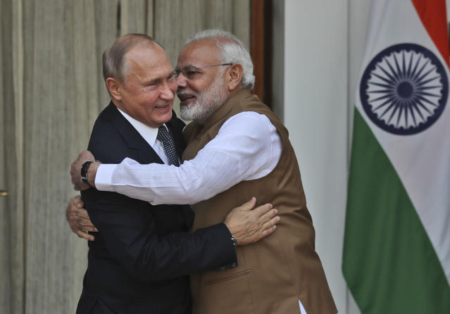 FILE - In this Oct. 5, 2018 file photo, Indian Prime Minister Narendra Modi, right, hugs Russian President Vladimir Putin before their meeting in New Delhi, India. Indian Prime Minister Narendra Modi's party claimed it had won re-election with a commanding lead in vote count Thursday, May 23, 2019. Modi, 68, the leader of the Hindu nationalist Bharatiya Janata Party, has carefully constructed an image of himself as a pious man of the people, a would-be monk called to politics who has elevated India's status globally and transformed its parliamentary elections from a contest of political parties on social and economic issues into a cult of personality. (AP Photo/Manish Swarup, File)