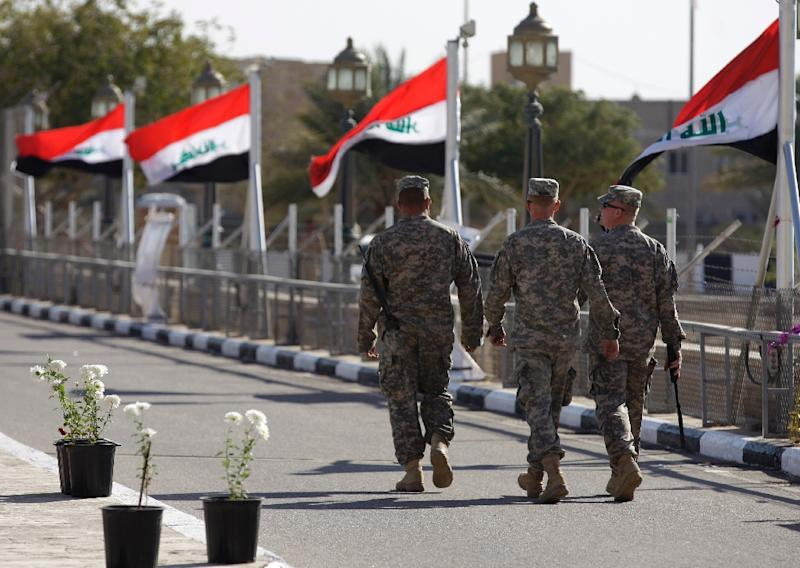 Iraqi flags fly in the wind as US soldiers walk at Camp Victory on December 1, 2011