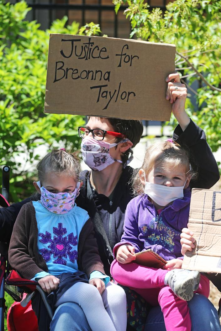 "Anne Schmidt of Milwaukee is joined by her twin daughters, Anya, left, and Naomi, 4, at the ""Sit-in for Change"" protest on Saturday."