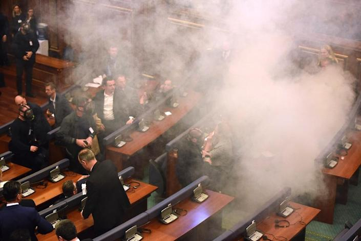 Members of the parliament disperse after tear gas was thrown by opposition lawmakers during an extraordinary session to elect Kosovo's new president, at the parliament in Pritsina on February 26, 2016 (AFP Photo/Armend Nimani)