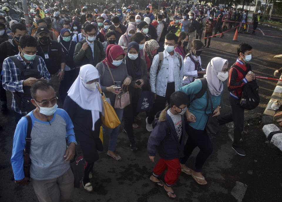 People wearing face mask to help curb the spread of coronavirus outbreak queue up to enter a commuter train station during the morning rush hour in Bekasi, Indonesia, Monday, Jan. 25, 2021. (AP Photo/Achmad Ibrahim)