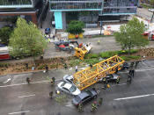 FILE - In this April 27, 2019, file photo, fire and police crew members work to clear the scene where a construction crane fell from a building on Google's new Seattle campus, crashing down onto one of the city's busiest streets and killing four people. Washington state's Department of Labor and Industries released the results of its investigation into the collapse Thursday, Oct. 17, 2019. It found, as experts have long suspected, that the crane toppled because workers who were disassembling it had prematurely removed pins securing the sections of the crane's mast. (AP Photo/Frank Kuin, File)