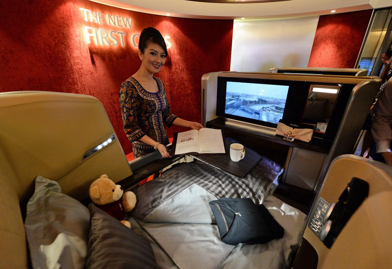 A Singapore Airlines (SIA) stewardess stands next to a display of the new Singapore Airlines First Class seat during their next generation cabin product launch in Singapore on July 9, 2013. SIA on July 9 unveiled new seats and other in-flight amenities as part of a sweeping upgrade of its cabins amid intensifying competition in the industry. AFP PHOTO / ROSLAN RAHMAN