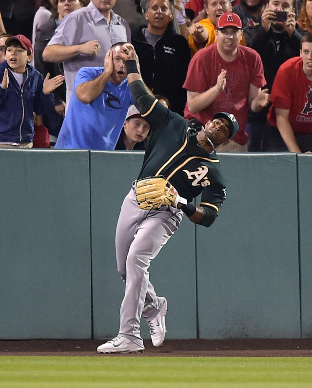 Oakland Athletics left fielder Yoenis Cespedes throws out Los Angeles Angels' Howie Kendrick at home plate during the eighth inning of a baseball game, Tuesday, June 10, 2014, in Anaheim, Calif. (AP Photo/Mark J. Terrill)
