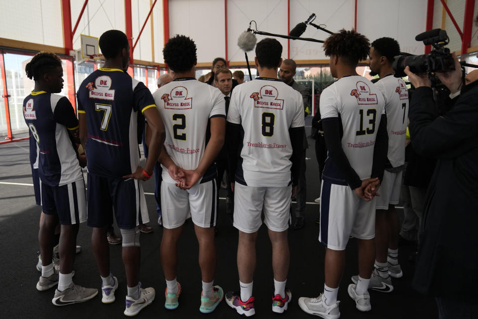 French President Emmanuel Macron, center, and former NBA player Tony Parker, center right behind, talk with members of a basketball team at a basketball playground in Tremblay-en-France, outside Paris, Thursday, Oct.14, 2021. French President Emmanuel Macron will promote sports ahead of the 2024 Olympic Games in Paris. (AP Photo/Francois Mori, Pool)