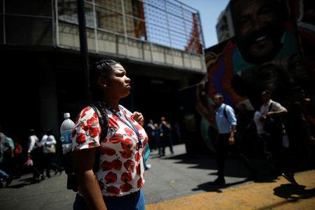 A woman stands in front of a closed metro station during a blackout in Caracas, Venezuela March 25, 2019. REUTERS/Carlos Garcia Rawlins