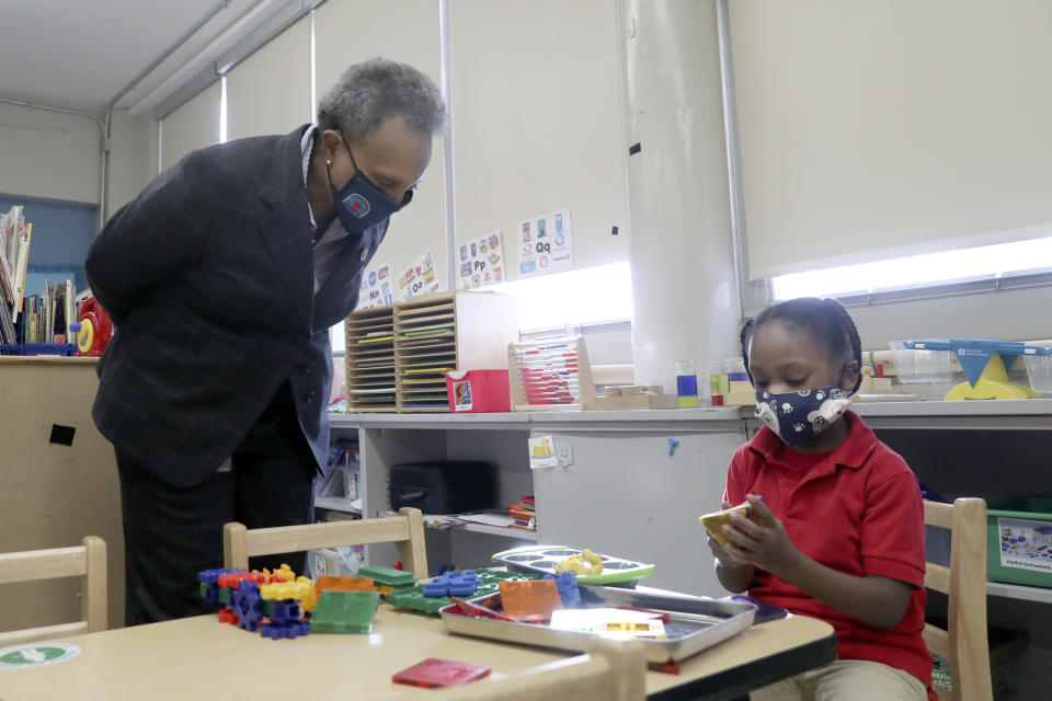 Chicago Mayor Lori E. Lightfoot talks with a student as they study in a William H. Brown Elementary School classroom Thursday, Feb. 11, 2021, during a school tour in Chicago. In-person learning for students in pre-k and cluster programs began Thursday, since the district's agreement with the Chicago Teachers Union was reached. (AP Photo/Shafkat Anowar, Pool)
