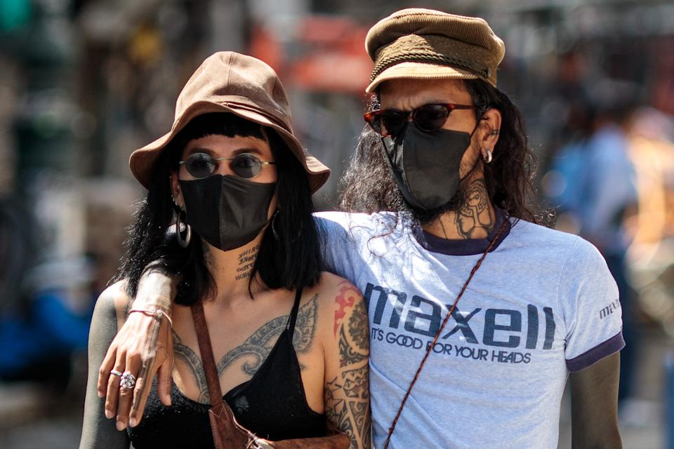 Tourists wearing facemasks amid concerns over the spread of the COVID-19 novel coronavirus walk along Khao San Road, a popular area for tourists in Bangkok on March 6, 2020. (Photo by Jack Taylor / AFP) (Photo by JACK TAYLOR/AFP via Getty Images)