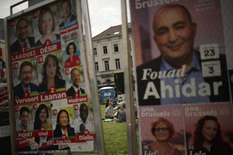 People sit on the grass near to political campaign posters near the European Parliament at the European quarter in Brussels, Thursday, May 23, 2019. Dutch and British voters were the first to have their say Thursday in elections for the European Parliament, starting four days of voting across the 28-nation bloc that pits supporters of deeper integration against populist euroskeptics who want more power for their national governments. (AP Photo/Francisco Seco)