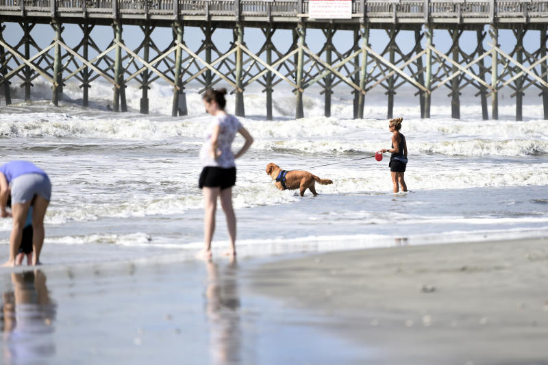 People walk near the pier at Folly Beach, S.C.,, Tuesday, Sept. 3, 2019, ahead of the arrival of Hurricane Dorian. The storm weakened to a Category 2 storm on Tuesday as it continued to batter the Bahamas with life-threatening storm surge. (AP Photo/Meg Kinnard)