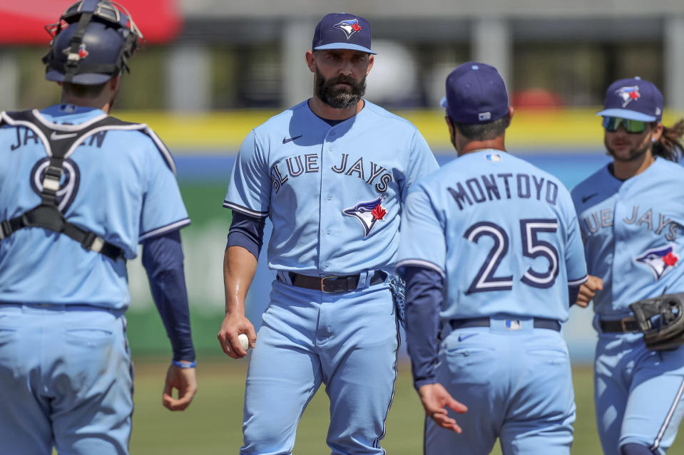 Toronto Blue Jays relief pitcher Tyler Chatwood, center, waits for manager Charlie Montoyo to remove him as catcher Danny Jansen (9) and Bo Bichette join them during the ninth inning of a baseball game against the Tampa Bay Rays Sunday, May 23, 2021, in Dunedin, Fla. (AP Photo/Mike Carlson)