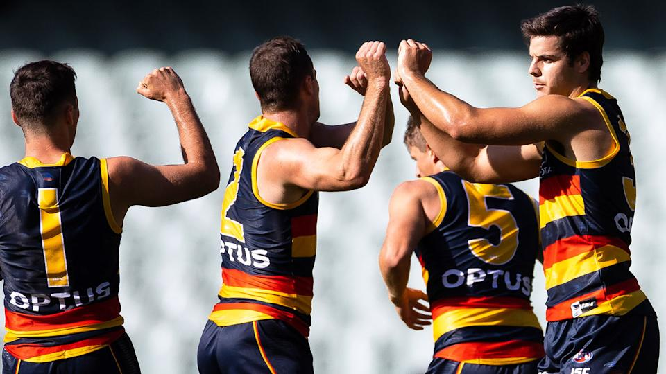 Pictured here, Adelaide Crows players celebrate during round one against the Sydney Swans.