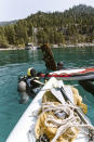 This photo provided by Clean Up The Lake shows a scuba divers hauling trash to the surface of Lake Tahoe, cleaning up trash on Friday, May 14, 2021. A team of scuba divers on Friday completed the first dive of a massive, six-month effort to rid the popular Lake Tahoe of fishing rods, tires, aluminum cans, beer bottles and other trash accumulating underwater. (Laura Visconti/Clean Up The Lake via AP)