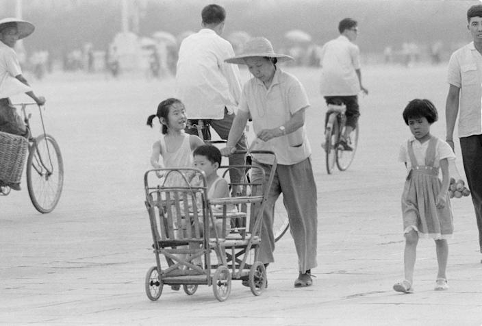 A mother wearing a straw hat pushes a buggy with a child sitting it. There are two other children walking near the buggy.