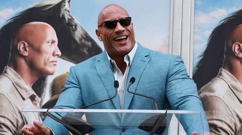 """Dwayne """"The Rock"""" Johnson in a blue suit and sunglasses"""