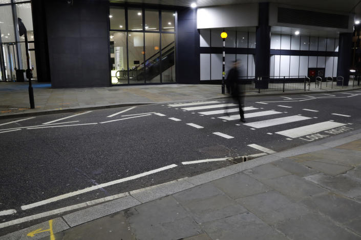 "A man walks on a pedestrian crossing in London, Saturday, March 6, 2021. When the pandemic struck, about 540,000 workers vanished from London's financial hub almost overnight. The area known as ""the City"" became a ghost town as many people began working from home. (AP Photo/Alastair Grant)"