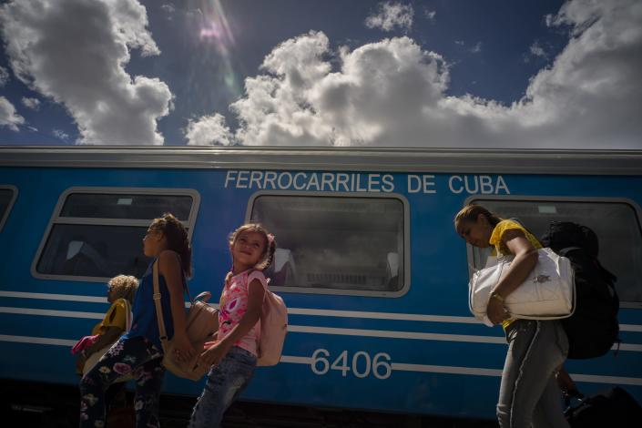 Passengers board the first train using new equipment from China , in Havana, Cuba, Saturday, July 13, 2019. The first train using new equipment from China pulled out of Havana Saturday, hauling passengers on the start of a 915-kilometer (516-mile) journey to the eastern end of the island as the government tries to overhaul the country's aging and decrepit rail system. (AP Photo/Ramon Espinosa)