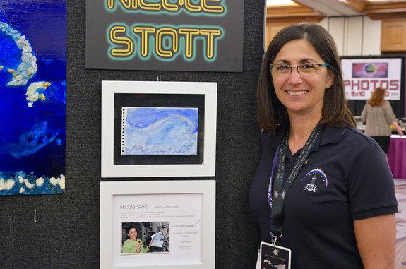 Nicole Stott poses with her original watercolor painted aboard the International Space Station in 2009.