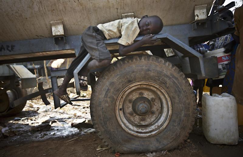 FILE - In this Tuesday, Dec. 31, 2013 file photo, a young displaced boy rests on the wheel arch of a water truck while others fill containers from it, at a United Nations compound which has become home to thousands of people displaced by the recent fighting, in the Jebel area on the outskirts of Juba, South Sudan. The fighting in the world's newest country has left thousands of its youngest citizens either orphans or separated from their parents, increasing their vulnerability to sickness, malnutrition and recruitment by warring groups as child soldiers. (AP Photo/Ben Curtis, File)