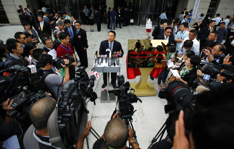 Gu Feng, CFO of SAIC Group, talks with reporters during a press conference after the inauguration of Shanghai's Free Trade Zone in Pudong district, Sunday, Sept. 29, 2013. China's first pilot free trade zone started operating in Shanghai on Sunday, billed as a test bed for the country's drive to deepen economic reform and providing a testing ground for free capital account convertibility of its currency. (AP Photo/Carlos Barria, Pool)