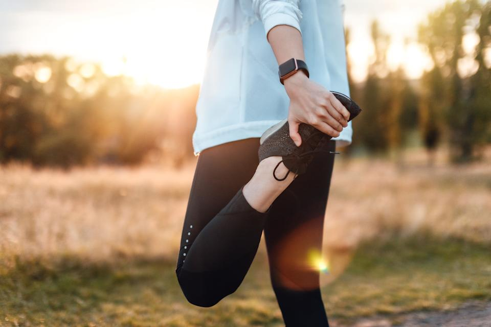 Cropped shot of a young confident woman stretching legs after running at the park, against sunlight at sunset.