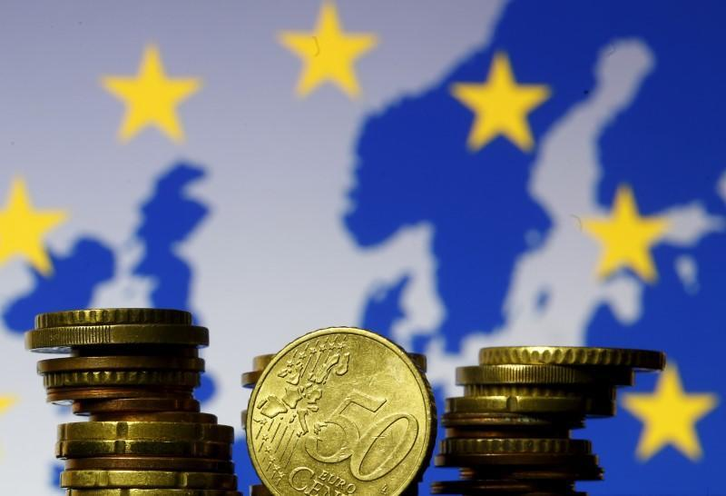 FILE PHOTO: Euro coins are seen in front of displayed flag and map of European Union in this picture illustration taken in Zenica