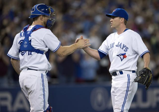 Toronto Blue Jays pitcher Casey Janssen, right, and catcher Erik Kratz celebrate after a baseball game against the Oakland Athletics on Friday, May 23, 2014, in Toronto. Toronto won 3-2. (AP Photo/The Canadian Press, Frank Gunn)