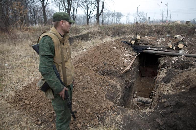 A pro-Russian gunman stands next to a trench in the Oktyaber neighborhood, northwest of Donetsk, near the destroyed airport, on November 13, 2014 (AFP Photo/Menahem Kahana)