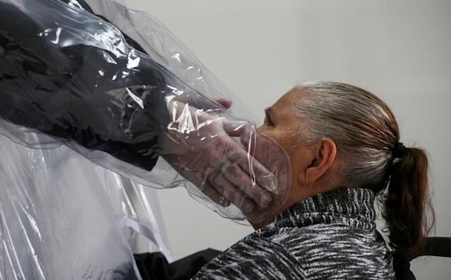 Ossimar Silva touches his mother Carmelita Valverde, 85, through a plastic curtain at the 3i Bem-Estar - Residencial Senior nursing home, amid the coronavirus disease (COVID-19) outbreak, in Sao Paulo, Brazil May 30, 2020. Picture taken May 30, 2020. REUTERS/Rahel Patrasso TPX IMAGES OF THE DAY