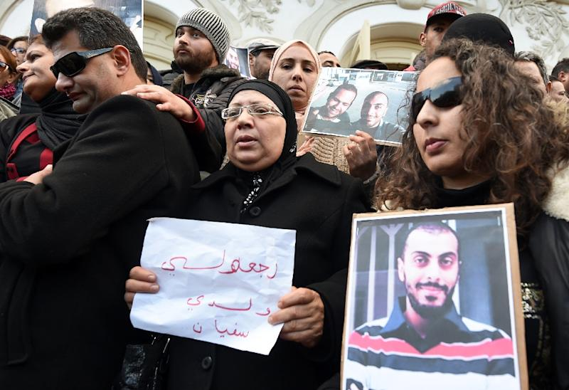 "Sofiene Chourabi's mother (C) holds a placard reading in Arabic: ""Bring back my son Sofiene"" during a demonstration in Tunis on January 9, 2015 (AFP Photo/Fethi Belaid)"