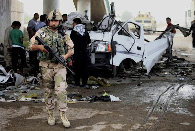 Civilians and security forces personnel gather at the scene of a car bomb attack in the Husseiniyah suburb of northeastern Baghdad, Iraq, Monday, May 6, 2013. Two car bombs blew up in a Baghdad suburb, killing and wounding dozens of people, police said, in the deadlier of two attacks Monday that left at least 10 dead in the Iraqi capital. (AP Photo/ Karim Kadim)