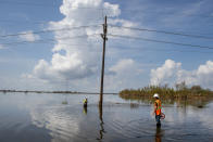 Utility crews stand in water as they work on repairing power lines along Highway 23 in Plaquemines Parish, La., over a week after Hurricane Ida on Tuesday, Sept. 7, 2021. (Chris Granger/The Times-Picayune/The New Orleans Advocate via AP)