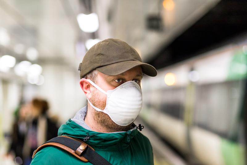 Male commuter waiting for train and wearing protective face mask in city railway station