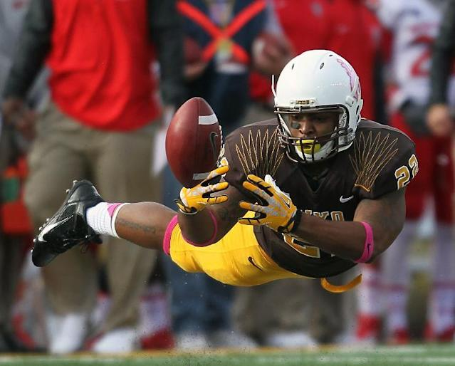 Wyoming running back Teddy Easton dives to catch a tipped pass in the fourth quarter against New Mexico in an NCAA college football game Saturday, Oct. 12, 2013, at War Memorial Stadium in Laramie, Wyo. (AP Photo/Wyoming Tribune Eagle, Blaine McCartney)