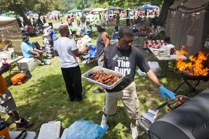 Jonathan Talley, of Roxbury, grills chicken, ribs, and sausage at Franklin Park for the Juneteenth celebration on Saturday afternoon, June 21, 2014. (Photo by Zack Wittman for The Boston Globe via Getty Images)