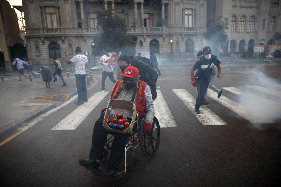 A protester helps a vendor in a wheelchair seek refuge from tear gas launched by police to disperse protesters near Congress where lawmakers swore-in a new president after voting to oust President Martin Vizcarra the day before, in Lima, Peru, Tuesday, Nov. 10, 2020. Peru swore in businessman and head of Congress Manuel Merino Tuesday who is unknown to most and was recently accused of trying to secure the military's support for a congressional effort to boot the nation's last leader out over unproven corruption allegations. (AP Photo/Rodrigo Abd)